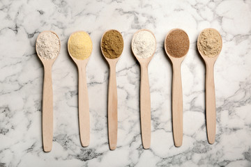 Spoons with different types of flour on marble background, top view