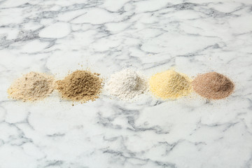 Piles of different flour types on marble table