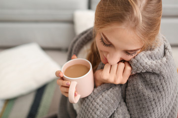 Beautiful young woman wrapped in plaid sitting with cup of coffee on floor at home. Winter atmosphere
