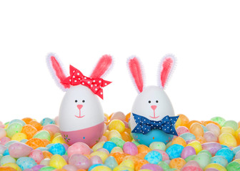 Easter Eggs crafted into bunnies, boy and girl, wearing bow tie and bow on ear sitting in a colorful pile of speckled jelly beans.
