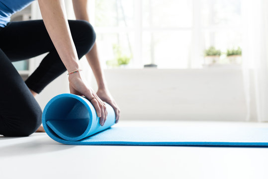 Young woman rolling her yoga mat after exercising