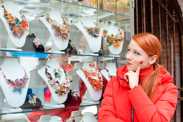 Thoughtful young woman looking at jewelry in the shop window in Italy Murano Island thinking which one to choose. Irish model in red winter coat clothing, redhead hair standing on urban background