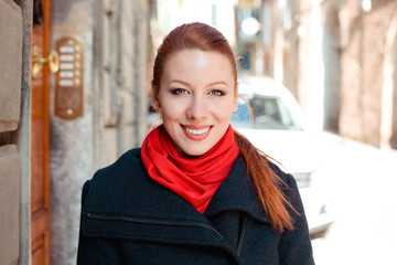 Beautiful woman in autumn style in town. Fashionable concept. Irish model in winter black dark blue coat clothing, red scarf, redhead hair standing on urban background. Smiling girl looking at camera