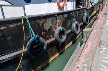 rubber tires hanging from side of old boat in harbor