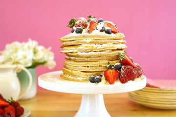 Shrove Pancake Tuesday, last day before Lent, stack of pancakes cake prepared with layers of whipped cream and fresh berries.