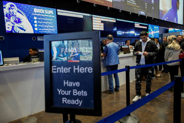 People make their bets at the FANDUEL sportsbook during the Super Bowl LIII in East Rutherford, New Jersey