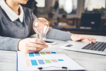 woman hand light bulb on office desk