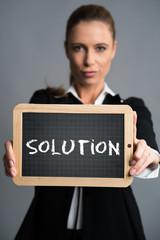 """junge Geschäftsfrau mit Nachricht """"Solution"""" auf Schiefertafel"""