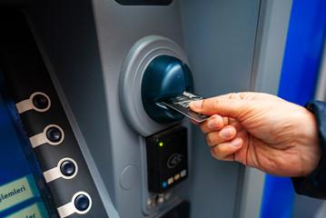 man pushing credit card at cash dispenser