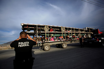 A police officer takes pictures of migrants as they arrive in the back of a truck to a provisional shelter during their journey towards the United States, in Saltillo, Mexico