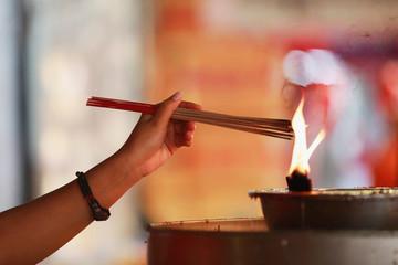 A woman lights incense sticks as she pray at a Chinese temple in Chinatown at Bangkok