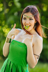 Beautiful young asian woman with slice of kiwi in mouth