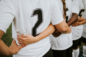Close up of female football players huddling