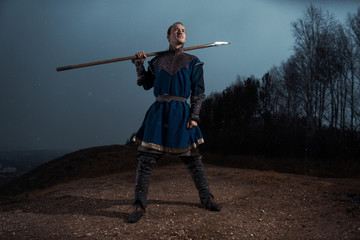 Medieval knight with sword and spear in ancient armour over Winter Landscapes