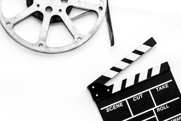 Filmings concept. Clapperboard and film stock on white background top view space for text