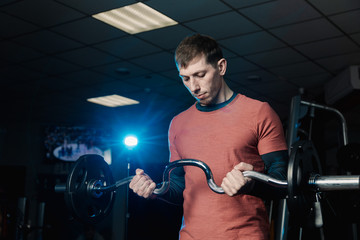 Handsome athletic man trains biceps barbell in the gym.