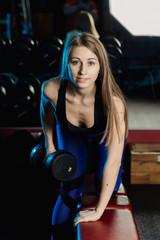 Side view of beautiful fitness woman workout with weights over exercise bench at gym.