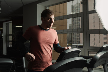 Handsome athletic man exercising on the treadmill in the gym.