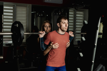 Active beautiful fitness model girl insists on squatting an athletic man in the gym.