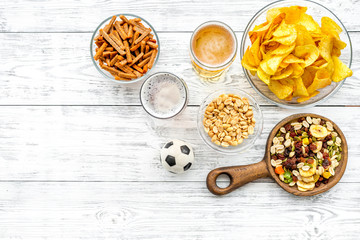 Snacks for watching football on TV. Watching sports. Chips, nuts, rusks near beer and soccer ball on white wooden background top view copy space