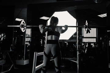 Active beautiful fitness model girl crouches with a barbell on the shoulders in the gym.