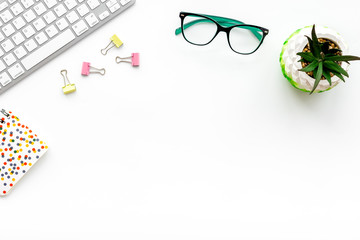 Work desk of creative person. Computer keyboard, glasses, bright stationery, plant on white background top view copy space