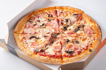 Italian fast food. Delicious hot pizza in a box with ham, champignons sliced and served on white table, close up view. Concept of fast and unhealthy diet