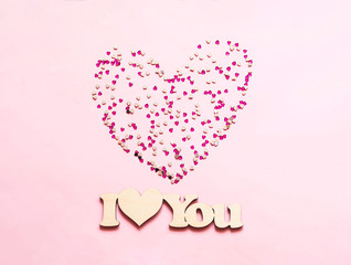 Festive pink background with spangles in the shape of heart. Concept Valentines Day or Mothers Day.
