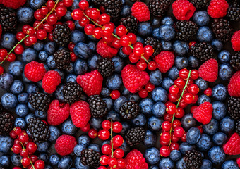 Berries overhead Background. Fresh Summer Berry mix with Strawberry, Raspberry, Red currant,  Blueberry and Blackberry, top view.
