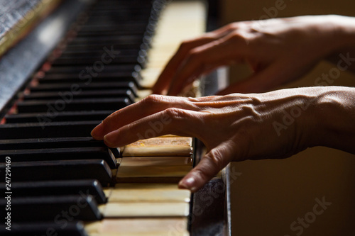 Close up fingers of woman pianist at the rusty piano keys