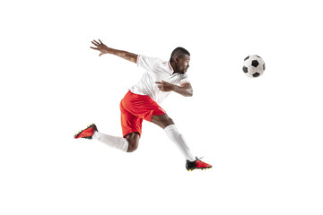 Professional african american football soccer player in motion isolated on white studio background. Fit jumping man in action, jump, movement at game.
