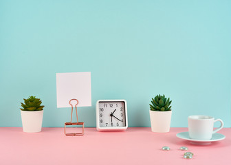 Mockup with white frame, note, alarm, cup of coffee or tea on pink table against blue wall with copy space.
