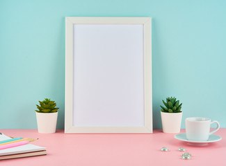 Mockup with blank white frame, plant cactus, cup of coffee or tea on pink table against blue wall with copy space.