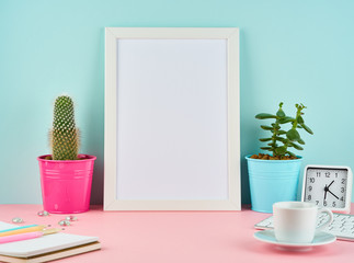 Mockup with blank white frame, alarm, notepad, cup of coffee or tea on pink table against blue wall with copy space.