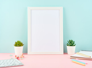 Mockup with blank white frame, alarm, notepad, keyboard on pink table against blue wall with copy space. Modern bright office desktop