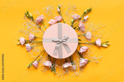 Happy Mother's Day, Women's Day, Valentine's Day or Birthday Yellow and Pastel Pink Colored Background. Flat lay greeting card with beautiful gift box and pink lisianthus flowers.
