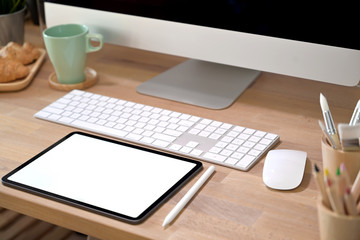 Office desk workspace with blank screen tablet and office supplies