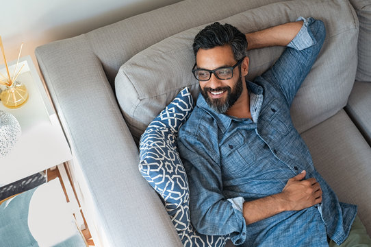 Mixed race man relaxing on couch