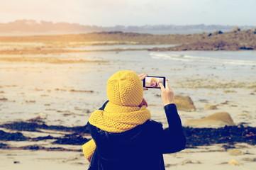 Eine Frau macht mit ihrem Smartphone ein Selfie am Strand