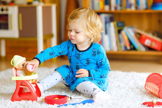 Adorable cute little toddler girl playing with doll. Happy healthy baby child having fun with role game, playing mother at home or nursery. Active daughter with toy.