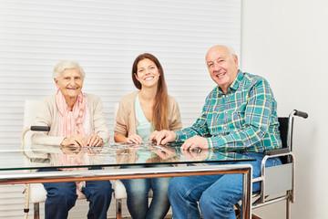 Wall Mural - Senioren und junge Frau spielen Puzzle spielen