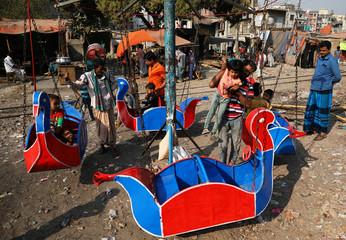 Children ride a merry-go-round in Dhaka