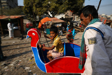 A child rides a merry-go-round in Dhaka