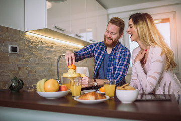 Happy couple make orange juice in morning kitchen and having a good time.