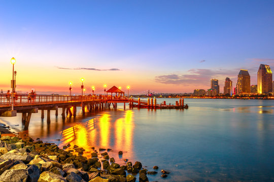 Scenic view of Coronado Ferry Landing on Coronado Island, California, USA. Downtown of San Diego at twilight on background. Old wooden pier reflecting on beach shore in San Diego Bay.