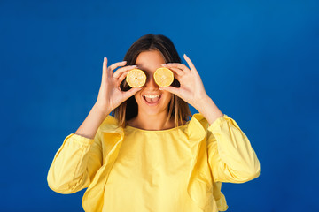 Portrait of laughing brunette in yellow blouse holding slices of lemon. Blue background.