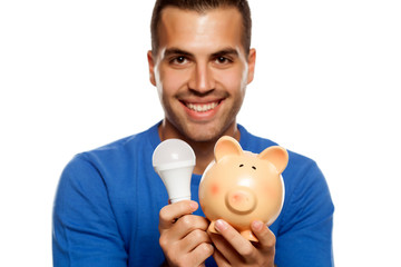 portrait of happy young man, holding LED bulb and piggy bank on white background