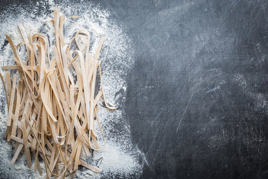 Raw uncooked homemade pasta with flour over dark background. Top view with space for text.