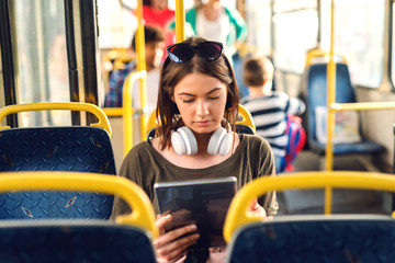 Pretty young girl with headphones sitting in a bus and watching tablet.