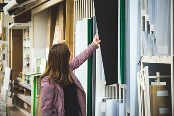 Woman at home building material choosing wood to renovate her home. Girl looking at choosing laminae from laminate finish texture inside the store for construction or renovation